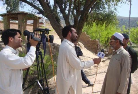 Said Nazir interviews a resident in Pakistan.